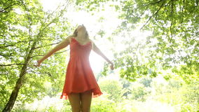 Beautiful teen twirling in the sunlight under the trees. In a forest stock footage