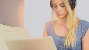 Beautiful teen using laptop on her sofa and listening to music Royalty Free Stock Image