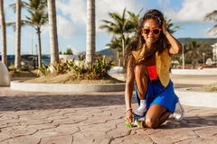 Beautiful teenage black girl in blue skirt with her penny longbo Royalty Free Stock Images