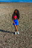 Beautiful teenage black girl in blue skirt and pink bra on the r Royalty Free Stock Photos