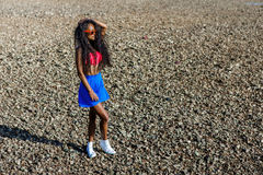 Beautiful teenage black girl in blue skirt and pink bra on the r Stock Image