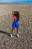 Beautiful teenage black girl in blue skirt and pink bra on the r Stock Images