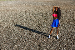 Beautiful teenage black girl in blue skirt and pink bra on the r Stock Photography