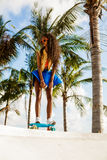 Beautiful teenage black girl in bright outfit rides at tropical Royalty Free Stock Photo