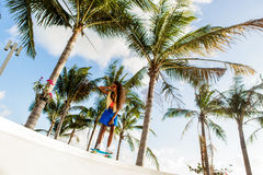 Beautiful teenage black girl in bright outfit rides at tropical Royalty Free Stock Image