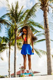 Beautiful teenage black girl in bright outfit rides at tropical Royalty Free Stock Photos