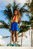 Beautiful teenage black girl in bright outfit rides at tropical Stock Images