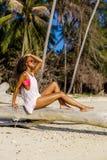 Beautiful teenage black girl sit on palm tree at the beach. Stock Photo