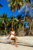 Beautiful teenage black girl sit on palm tree at the beach. Royalty Free Stock Image