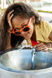 Beautiful teenage black girl in sunglasses drinking from water d Royalty Free Stock Photo