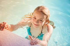 Beautiful teenage blond girl swims in pool Royalty Free Stock Image