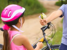 Beautiful teenage boy in protective bicycle helmet and girl in a park, boy giving flowers to the girl. Friendship stock photography