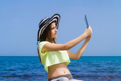Beautiful teenage brunette using a tablet by the Royalty Free Stock Image