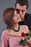Beautiful teenage couple. Happy beautiful teenage couple, a boy giving a rose to his girlfriend and kissing her Royalty Free Stock Image