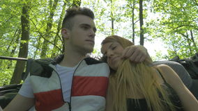 Beautiful teenage couple enjoying nature in a convertible car stock video footage