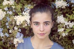 Beautiful teenage girl in a blooming bush Stock Photo