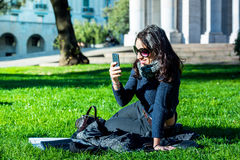 Beautiful teenage girl with dark hair and sun glasses looking at her smartphone Royalty Free Stock Photography