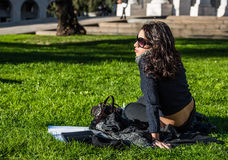 Beautiful teenage girl with dark hair and sun glasses sitting in a public garden Royalty Free Stock Photography