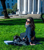 Beautiful teenage girl with dark hair and sun glasses sitting in a public garden Stock Photo