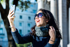 Beautiful teenage girl with dark hair and sun glasses taking selfies and laughting - close shot Royalty Free Stock Images