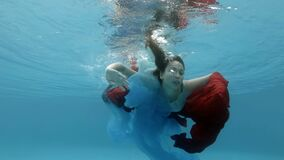 A beautiful teenage girl in a dress swims underwater in a swimming pool, plays with a red and blue cloth near the surface. And looks at the camera. The view stock video footage