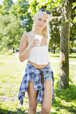 Beautiful teenage girl drinking coffee in park Stock Images