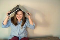 Beautiful teenage girl full body working behind laptop royalty free stock image