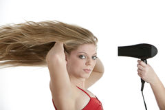 Beautiful teenage girl having her hair blow dried Royalty Free Stock Images