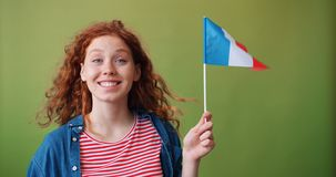 Beautiful teenage girl holding flag of France smiling looking at camera. Female French patriot beautiful teenage girl holding flag of France smiling looking at stock video footage