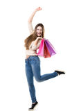 Beautiful teenage girl jumping high with delight holding pink sh. Beautiful teenage girl with broad happy smile jumping with joy, holding heap of shopping bags Stock Images