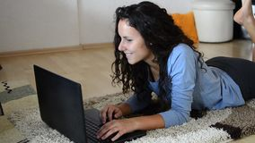 Beautiful teenage girl laying on floor using laptop stock video