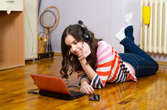 Beautiful teenage girl listening to music while lying on floor Royalty Free Stock Images