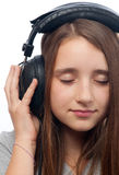 Beautiful teenage girl listens to music Stock Images