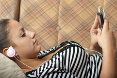 Beautiful teenage girl listens to music on phone Stock Photos