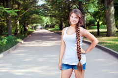 Beautiful teenage girl with long braid in the park Stock Images