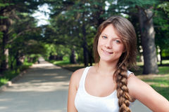 Beautiful teenage girl with long braid in the park Stock Photography