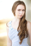 A beautiful teenage girl with long brown curled hair pulled to the side with a blue long dress. Stock Images