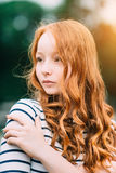 A beautiful teenage girl with long curly ginger hair. And green eyes hugging herself in summer park. Outdoor portrait of attractive red-haired young woman in stock photography