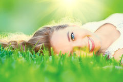 Beautiful teenage girl lying on green grass Royalty Free Stock Photos