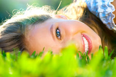 Beautiful teenage girl lying on green grass Royalty Free Stock Photo