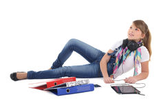 Beautiful teenage girl lying and listening music with tablet pc Royalty Free Stock Images