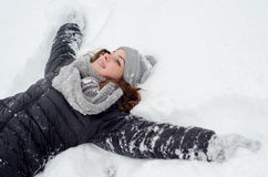 Beautiful teenage girl lying in the snow Royalty Free Stock Photography