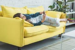 Beautiful teenage girl lying on sofa. And using smartphone stock photo