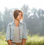 Beautiful teenage girl outdoors. Portrait of beautiful teenage girl outdoors in jeans wear looking away Stock Images