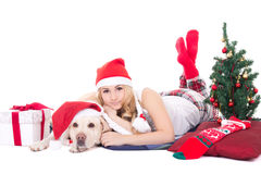 Beautiful teenage girl in pajamas lying with dog in santa hat is Stock Photos
