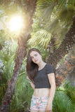 Beautiful teenage girl with palm trees and sun Royalty Free Stock Photo