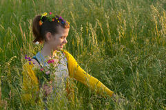 Beautiful teenage girl picking flowers on meadow. Beautiful teenage girl picking flowers on the meadow on sunny spring day Stock Photo