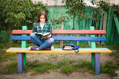Beautiful teenage girl reading book. Outdoors in summer Royalty Free Stock Images