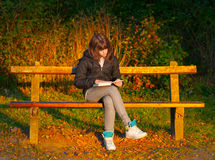 Beautiful teenage girl reads the book in the park Royalty Free Stock Photo