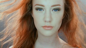 Beautiful teenage girl with red blowing hair and. Blue eyes on grey studio background. 4K RAW Blackmagic Production Camera stock video